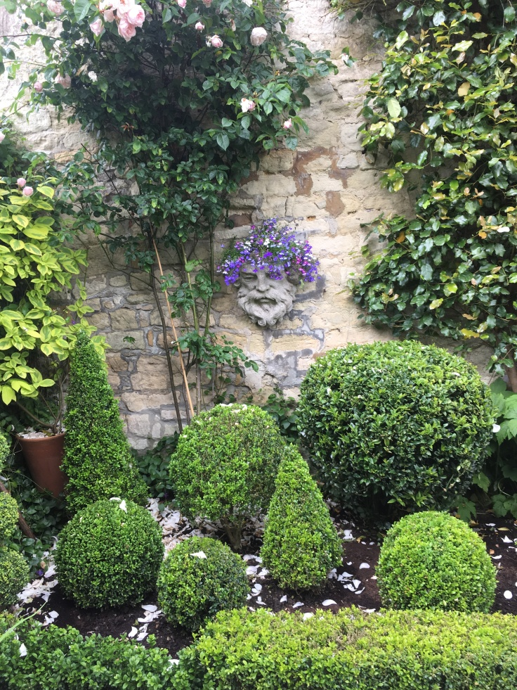 stone wall with decorative head planted with lobelia surrounded by ivy and topiary